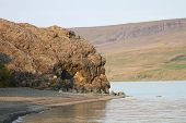 picture of troll  - Scenic View of Sleeping Troll Rock Formation Along Shoreline Drenched in Warm Sunlight in Iceland - JPG