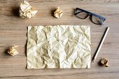 pic of stress-ball  - Crumpled paper balls with eye glasses on wood desk creative writing concept - JPG