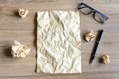 foto of stress-ball  - Crumpled paper balls with eye glasses on wood desk creative writing concept - JPG