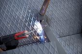 pic of welding  - Two men working over iron platform with arc welding - JPG