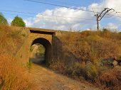 stock photo of underpass  - Railway bridge underpass leading into lemon grove near Alora Andalucia - JPG