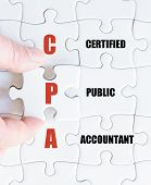 picture of cpa  - Hand of a business man completing the puzzle with the last missing piece - JPG
