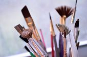 stock photo of stippling  - Bouquet of many small paintbrushes of various sizes and shapes standing upright in art studio. Closeup of art supplies well worn and used by an artist candid and realistic shot. Mostly neutral colors with some purple pink and green handles.