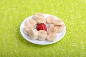 stock photo of bunch bananas  - Bunch of bananas and several strawberries on white plate - JPG