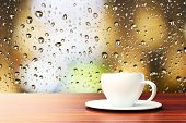 image of raindrops  - cup of coffee on the background of the window with raindrops - JPG