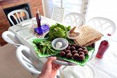 pic of seder  - Man hand carry Passover Seder Plate with The seventh symbolic item used during the Seder meal on passover Jewish holiday - JPG
