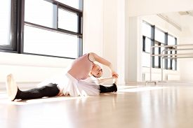 picture of  dancer  - Young Pretty Ballet Dancer Doing Stretching Exercise on the Floor Inside the Studio with Legs Split and Body Bent on her Side - JPG