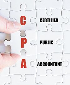 stock photo of cpa  - Hand of a business man completing the puzzle with the last missing piece - JPG