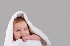 picture of teething baby  - smiling baby teething bites the hand in a white towel isolated on gray background - JPG