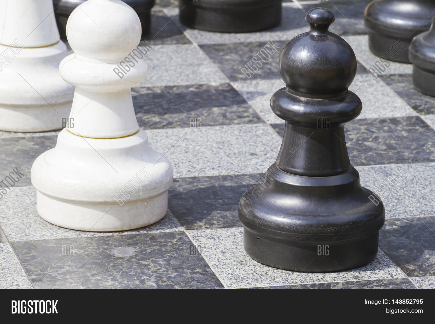 close up of life sized chess pieces on chess board stock