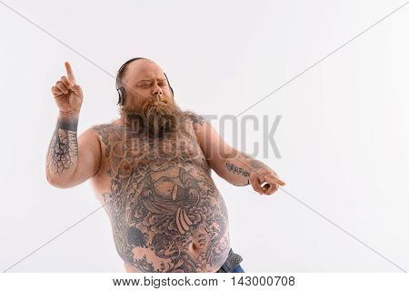 Thick bearded man is dancing while listening to music. He is moving arms and relaxing. His eyes are closed with enjoyment. Isolated and copy space in right side