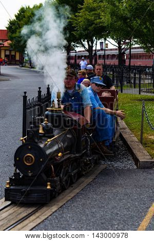 Strasburg PA - July 19 2016: Visitors ride on a small working steam train at the Strasburg Rail Road.