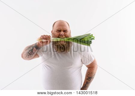 Hungry thick man is biting leek. He is standing and looking at camera with desire. Isolated