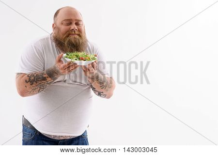 Fat man is holding plate of salad and smelling it with pleasure. He is standing with closed eyes. Isolated and copy space in left side