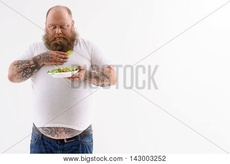 Thick bearded man is looking at plate of salad with shock. He is standing and carrying fork. Isolated and copy space in right side
