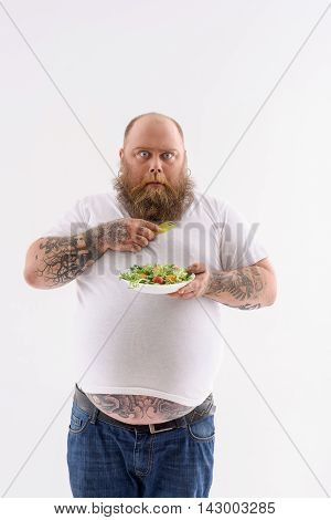 This is the worst diet ever. Scared fat man is holding plate of salad and looking at camera with fear. Isolated