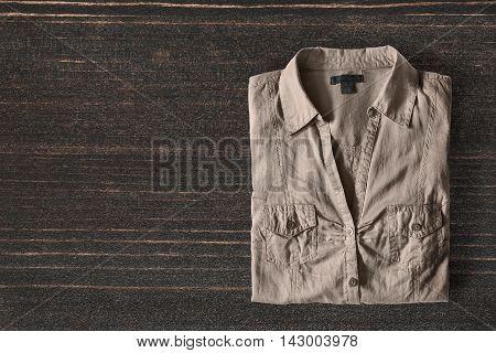 Folded khaki shirt on dark wooden background