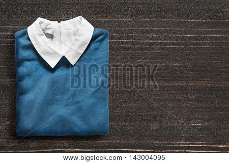 Folded blue pullover on dark wooden background