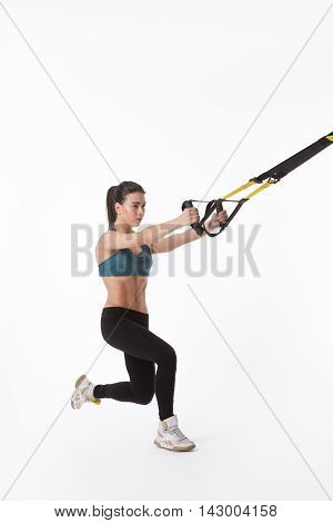 Picture of young beautiful woman training with suspension trainer sling isolated on white background. Upper body excercise concept. TRX concept. Studio shot.