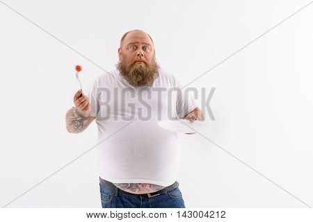Unfortunately it is the last tomato. Hungry thick man is holding vegetable on fork and empty plate. He is standing and looking at camera with sadness. Isolated