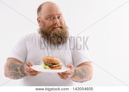 This food makes me happy. Joyful fat man is showing plate with appetite sandwich. He is standing and smiling. Isolated and copy space in right side