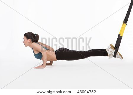 Core body excercise concept. Lady posing for photographer in studio. Beautiful lady training with suspension trainer sling or suspension straps.