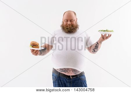 Thick guy is choosing between hamburger and salad. He is standing and looking at sandwich with appetite. Isolated