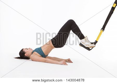 Core body excercise concept. Picture of young lady exercising with suspension trainer sling isolated on white in studio. Beautiful woman practicing popular sport with suspension straps.