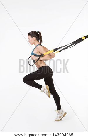 TRX concept. Picture of fitness trainer posing for photographer while training with suspension trainer sling or suspension straps.