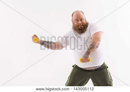 Serious fat man is doing exercise with dumbbells. He is standing and looking at camera seriously. Isolated