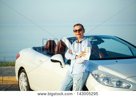 Young formal dressed woman in bow tie standing with a map in hand near the white convertible