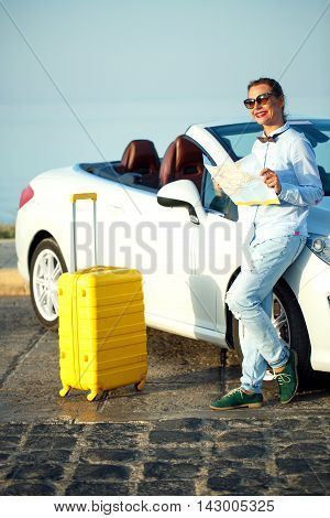 Young formally dressed woman with a yellow suitcase looking to map near the white convertible