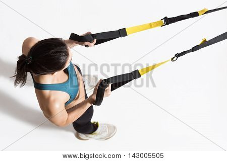 Top view of pretty young lady training upper body on suspension trainer sling. Beautiful woman excercising in studio. Lady using TRX equipment.