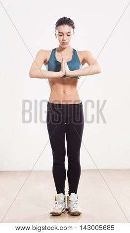 Practicing yoga. Young woman isolated on white background. Beautiful woman with her hands clasped in front of her.