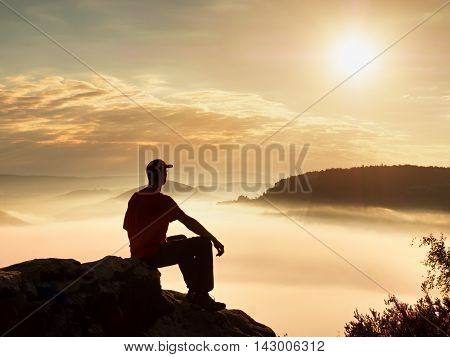 Man tourist sit on rock empire. View point with heather and branches above misty valley. Sunny daybreak in rocky mountains.