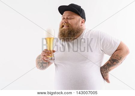 Joyful fat man is drinking beer and smiling. His eyes are closed with pleasure. Isolated and copy space in left side