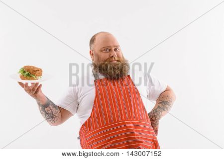 Cheerful fat male chef is presenting plate with burger. He is standing in apron and looking at camera with confidence. Isolated