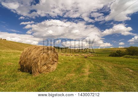 a harvest landscape vista in rolling hills in Romania with round straw bales and patchwork fields under a blue cloudy sky in summer