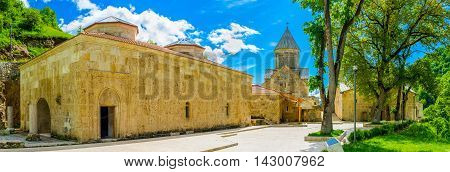 The huge stone Refectory and the St Astvatsatsin (Mother of God) Church of the Haghartsin Monastery on the background Armenia.