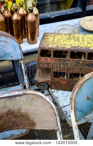Collectible antiques for sale at Portobello Market London UK in a close up view of a rusted toy bus on old chairs
