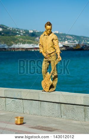 YALTA UKRAINE - MAY 25, 2013: Human statue (live artist as guitarist) on the sea-front earn some money letting campers to take photographs with them in Yalta, Ukraine at May 25, 2013.