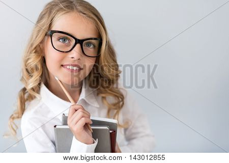Dreams come true. Close up of an ambitious little girl with glasses looking up and dreaming while standing with a pencil and notebooks on the grey background