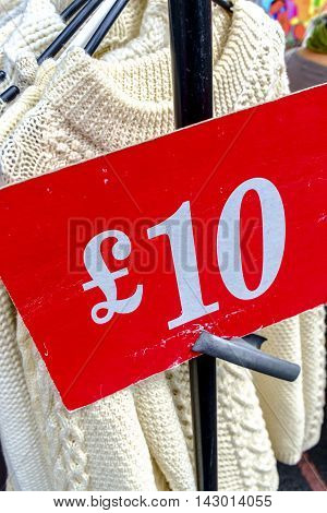 Ten pound price sign at the market on an outdoor rack of woollen jerseys for sale on a stall in London UK