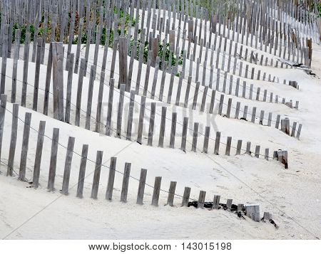 Wooden picket fence buried by drifting sand