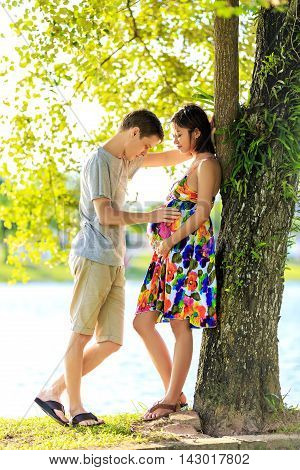 Happy Pregnant Couple Standing At Ttopical Park In Back Light