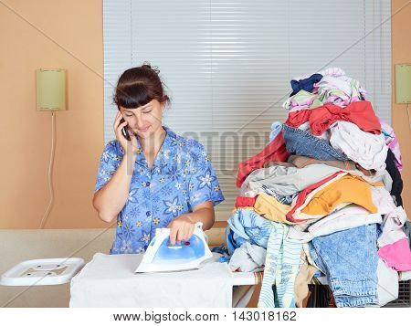 Caucasian Young Woman Ironed Clothes And Talking On The Phone.