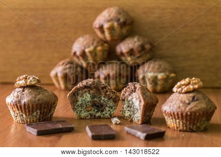 Bicolor muffins with chocolate, poppies and walnuts on table. Pyramid of muffins behind.