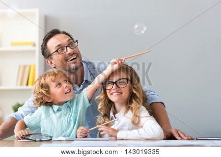 Lift it higher. Joyful little boy trying to catch a soap bubble with a pencil while sitting at the table with a smiling man and adorable girl