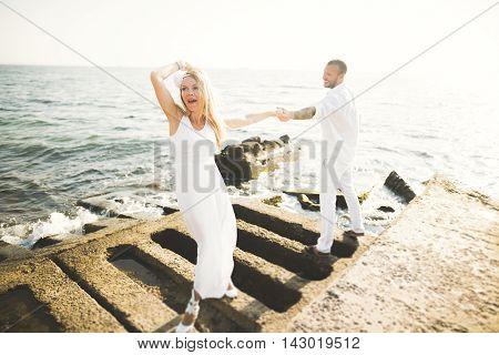 Fashion model couple with tattoo posing outside nea sea .