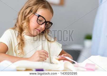 So serious. Thoughtful little lady with glasses sewing while sitting at the table